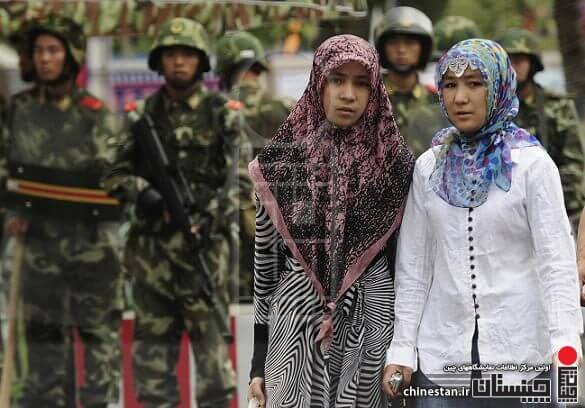 Two ethnic Uighur women pass Chinese paramilitary policemen standing guard outside the Grand Bazaar in the Uighur district of the city of Urumqi in China's Xinjiang region on July 14, 2009. A mosque was closed and many businesses were shuttered a day after police shot dead two Muslim Uighurs, as ethnic tensions simmered in restive Urumqi.   AFP PHOTO / Peter PARKS (Photo credit should read PETER PARKS/AFP/Getty Images)